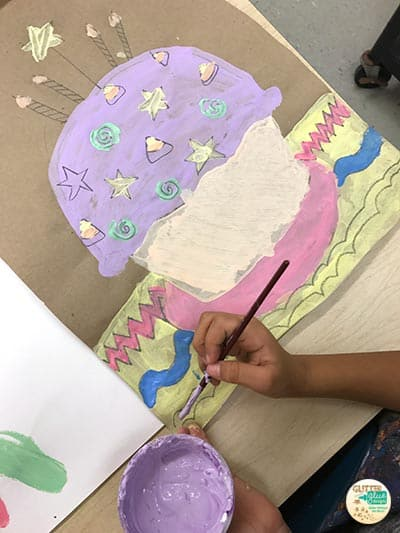 Second grade painting tints and shades on a cupcake.