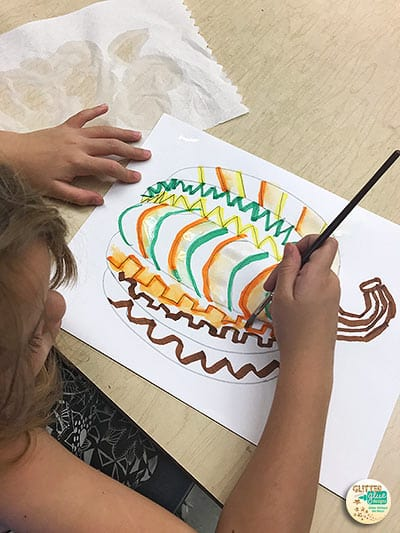first grade kid painting a pumpkin with markers