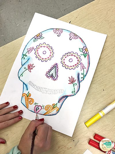 student painting her sugar skull using marketing painting technique
