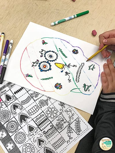 student coloring his sugar skull using symbols from worksheet