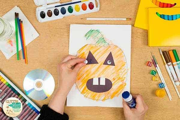 Glue googly eyes onto the pumpkin.