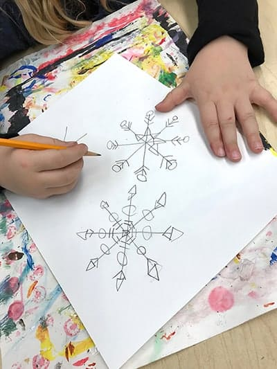 Kinders using geometric shapes and lines to draw a snowflake