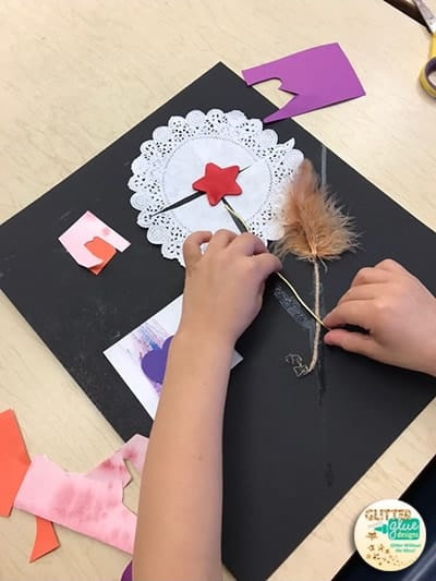 Kindergarten student using foam shapes, features, and doilies for a collage.