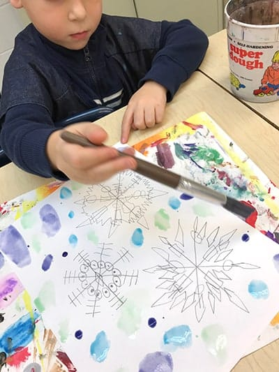 kindergarten using liquid watercolors to paint snowflakes