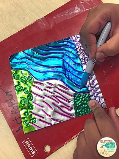 Student coloring in his repousse art project using permanent markers.