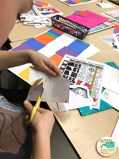 Students cutting out collage pieces.