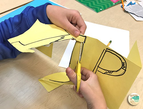 student cutting his onomatopoeia pop art letters out using scissors