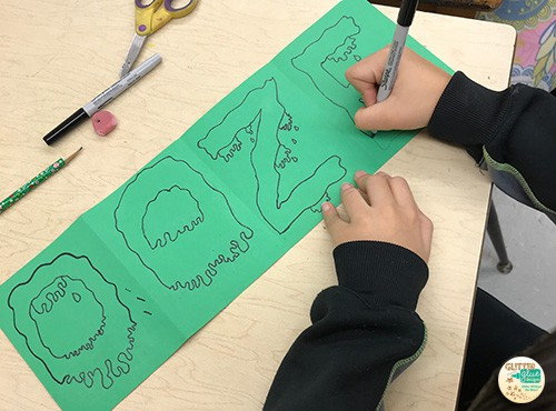 student writing onomatopoeia word ooze on green paper for slime