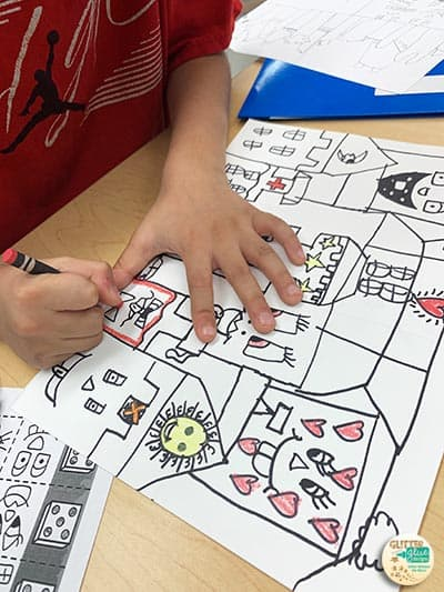 a students coloring in his cityscape artwork